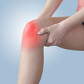 Acute pain in a woman knee holding hand to spot of aches Royalty Free Stock Photography