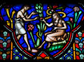 Adam and eve eating the forbidden fruit in the garden of eden on a stained glass window in the cathedral of brussels Royalty Free Stock Images
