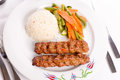 Adana kebabs served on a lavash bread garnished with vegetables turkish kebap rice pilaf and plate Stock Photos