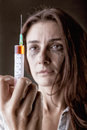 Addict young woman with drug addiction on dark backgroundю focus on syringe Stock Photo