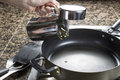 Adding cooking oil in frying pan Stock Photo