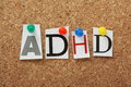 Adhd the abbreviation for attention deficit hyperactivity disorder in cut out magazine letters pinned to a cork notice board Stock Image