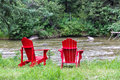 Adirondack chairs at shore of a river Stock Image