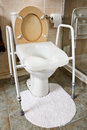 Adjustable height toilet seat which can be fitted over your existing fitting often used by the elderly or disabled to aid in Royalty Free Stock Image