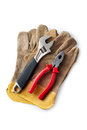 Adjustable wrench and pliers on protective gloves on a white background Royalty Free Stock Photo