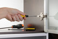 Adjusting a concealed hinge man uses screwdriver to adjust fixed on modern cabinet with glass door Royalty Free Stock Photos