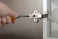Adjusting a concealed hinge man uses screwdriver to adjust fixed on modern cabinet with glass door Royalty Free Stock Images