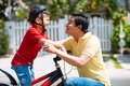 Adjusting helmet father of his son before biking Royalty Free Stock Image