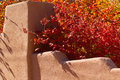 Adobe wall with autumn leaves red and yellow above a traditional stair step in santa fe Royalty Free Stock Photography