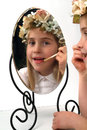 Adolable little girl looking in a mirror puts lipstick Stock Photography