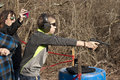 Adolescent boy with pistol at the ready wearing ear and eye protection shooting in front of wooded background coaches Royalty Free Stock Images