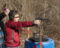 Adolescent boy shooting pistol wearing ear and eye protection in front of wooded background Royalty Free Stock Photography