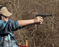 Adolescent girl shooting pistol with brass flying wearing ear and eye protection in front of wooded background Royalty Free Stock Images