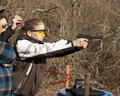 Adolescent girl shooting pistol with brass flying wearing ear and eye protection in front of wooded background coaches Stock Photography