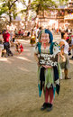 Adopt a jester performer in costume wanders through the crowd entertaining onlookers at the bristol renaissance fair in wisconsin Royalty Free Stock Images