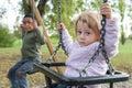 Adoptive brothers on the swing sat oscillation Stock Photo