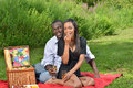 Adorable african american couple on picnic cute having a in a park women in black dress men in button up shirt women eating a Stock Images