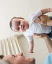 Adorable baby being carried by father low angle view of boy at home Stock Photo