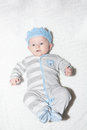 Adorable baby with blue crown boy eyes wide open up close on his back wearing and a warm winter sleep and play suit Royalty Free Stock Image