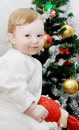 Adorable baby boy and Christmas tree Royalty Free Stock Photo