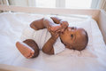 Adorable baby boy lying in his crib chewing foot Royalty Free Stock Photo