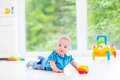 Adorable baby boy playing with colorful ball and toy car
