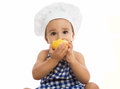Adorable baby with chef s cap eating pear isolated Royalty Free Stock Image