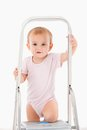 Adorable baby girl climbing on ladder in bodysuit smiling Royalty Free Stock Photo