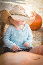 Adorable baby girl with cowboy hat at the pumpkin patch in a country rustic setting Royalty Free Stock Photography