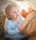 Adorable baby girl with cowboy hat at the pumpkin patch in a country rustic setting Royalty Free Stock Photos