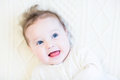 Adorable baby girl with curly hair on a white cabl Royalty Free Stock Photo