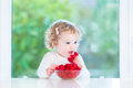 Adorable baby girl eating raspberry at white table Royalty Free Stock Photo
