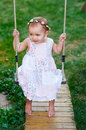 Adorable baby girl enjoying a swing ride on a playground in a park Royalty Free Stock Photo