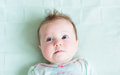 Adorable baby girl on a green knitted blanket smiling Royalty Free Stock Photography