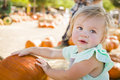 Adorable baby girl having fun at the pumpkin patch in a rustic ranch setting Royalty Free Stock Photography