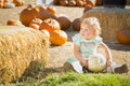 Adorable baby girl holding a pumpkin at the pumpkin patch in rustic ranch setting Stock Photography