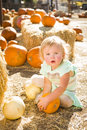 Adorable baby girl holding a pumpkin at the pumpkin patch in rustic ranch setting Stock Images