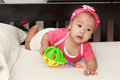 Adorable baby girl infant playing toy at nursery asian on the bed child Stock Photo