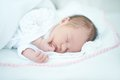 Adorable baby girl is sleeping on bed white Stock Image