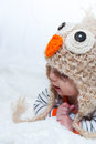 Adorable baby looking to the side in owl hat lying on his stomach Stock Photo