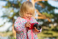Adorable baby shoot compact camera in park Stock Photos