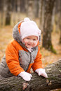 Adorable baby stay near fallen tree Stock Images