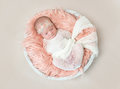 Adorable baby swaddled with white blanket, topview