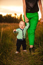 Adorable baby walking around with mother very cute boy smiling and having fun his outside making first steps Stock Photography