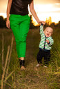 Adorable baby walking around with mother very cute boy smiling and having fun his outside making first steps Royalty Free Stock Photo
