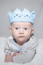 Adorable baby wearing blue knit crown with eyes lying on his stomach a light hat playing king Stock Photography