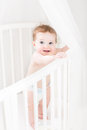 Adorable baby wearing a diaper standing in a white round crib ottle Stock Image