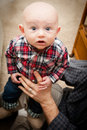 Adorable bald baby boy with big blue eyes wide open looking upward wearing a plaid shirt and jeans Royalty Free Stock Photo