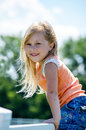 Adorable blond child on fence little girl poses a white Stock Photo
