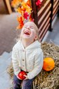 Adorable blonde baby toddler in white knittes jacket sitting on the haystack with pumpkins at porch, playing with apple and Royalty Free Stock Photo